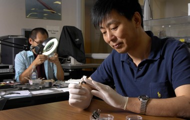 Xiaodong Li (foreground) demonstrates the flexibility of a swatch of activated carbon textile