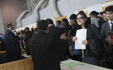 (REUTERS/Andrew Burton) Alena Slipenskaya, a senior majoring in international relations at City College Of New York, speak to a spokesman at Foreign Policy Association during the 2012 Big Apple Job and Internship Fair at the Javits Center in New York, April 27, 2012.