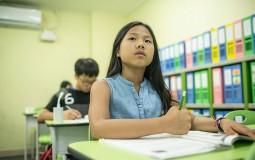 A student listens to the math teacher (not shown) at a math school