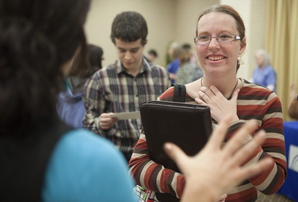 College graduate Rachel Westrick talks to a potential employer at a job fair in 2011