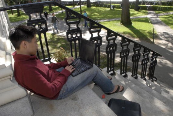 College student works on his laptop outside the classroom
