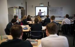 A teacher talks to pupils during a maths lesson