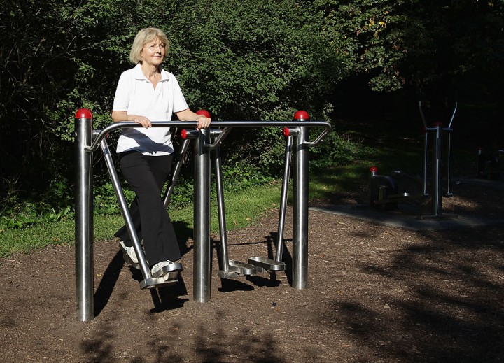 An elderly lady trains on an exercise device