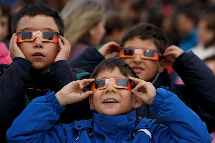 Children use protective glasses to look into the sky during a partial solar eclipse