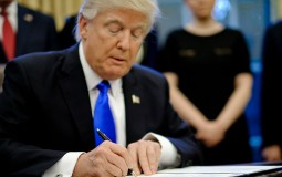 President Donald Trump signs three executive actions in the Oval Office on January 28, 2017 in Washington, DC. T
