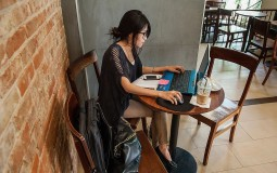 A student taking an online class inside a cafe.