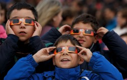 Children use protective glasses to look into the sky during a partial solar eclipse outside the Planetario