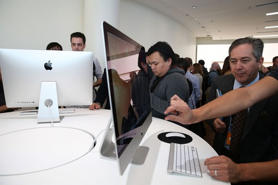 Attendees inspect the new 27 inch iMac with 5K Retina display during an Apple special event